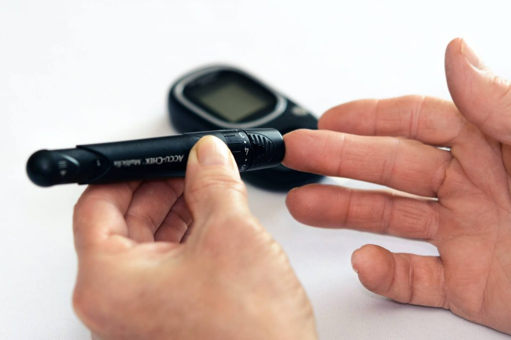 image of glucometer and fingerstick